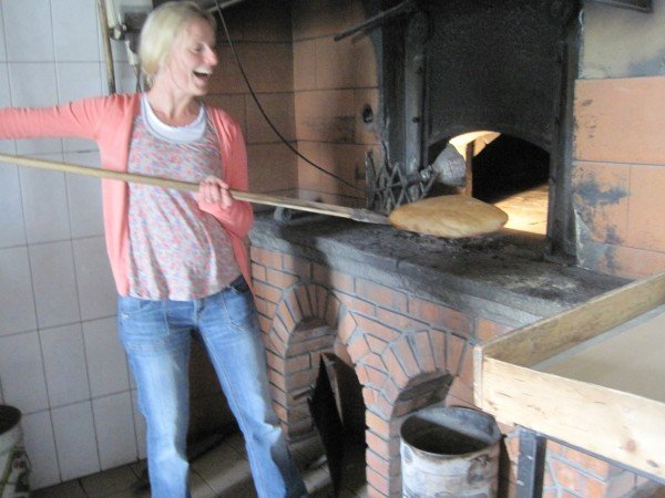 Taking bread from wood-fired oven