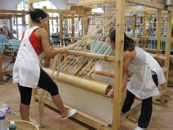 Artes weavers warping a loom.