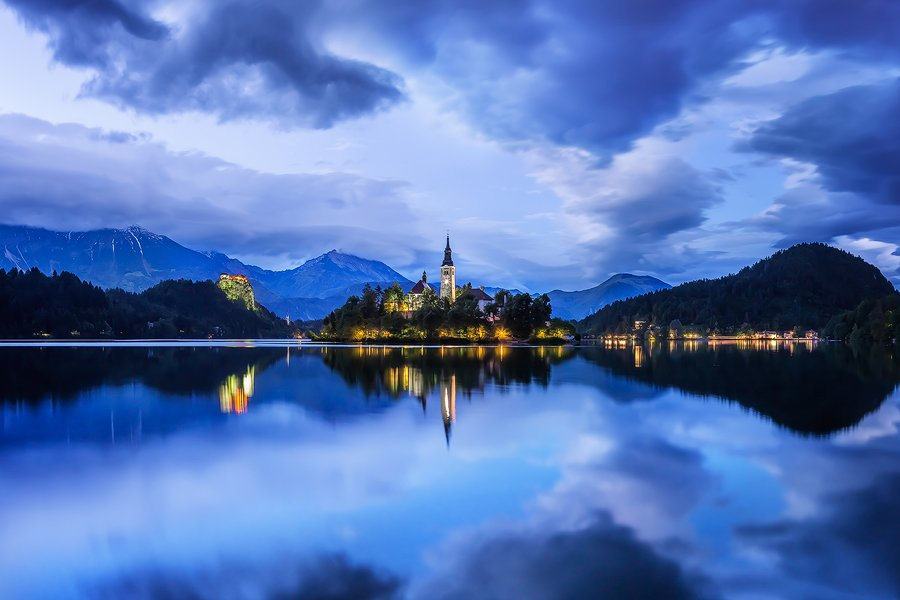 Lake Bled, Slovenia. While on a walk in pouring rain I put on my raingear and brought my camera and tripod. Thirty minutes into the walk the rain stopped and the sky opened up to reveal this wonderful Blue Light scene.