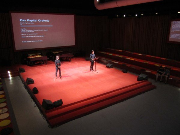 """Arena"" A large red stage with bleacher seating and a balcony in which various readings and performances are held."