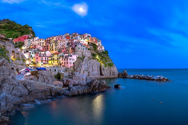 Manarola with the moon rising during the evening blue hour